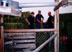 three men behind fence